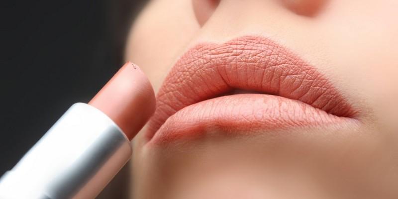 Frau trägt Lippenstift auf
