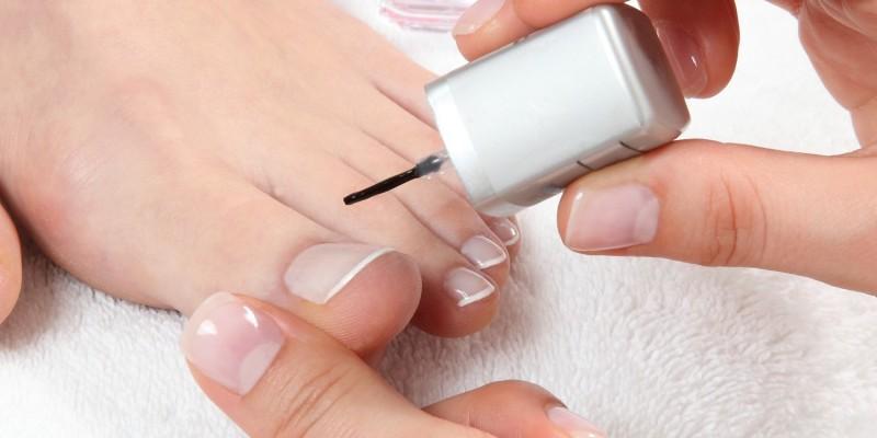 Kosmetikerin lackiert die Zehnägel